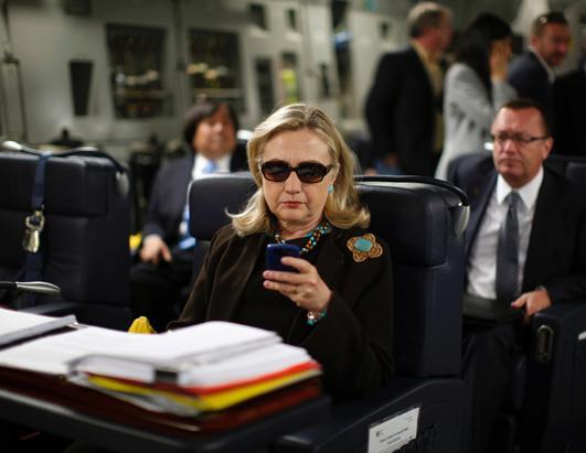 2011年10月18日,美国国务卿希拉里在即将从马耳他飞往的黎波里的军用C-17飞机上查看她的PDA。(Kevin Lamaeque/AFP/Getty Images)