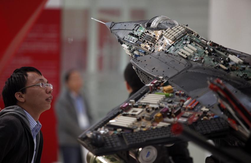 一名参观者欣赏由芯片,电路板等元器件制作的工业雕塑.