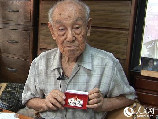 小林宽澄向人民网记者展示中国人民解放军纪念勋章 (赵松 摄)