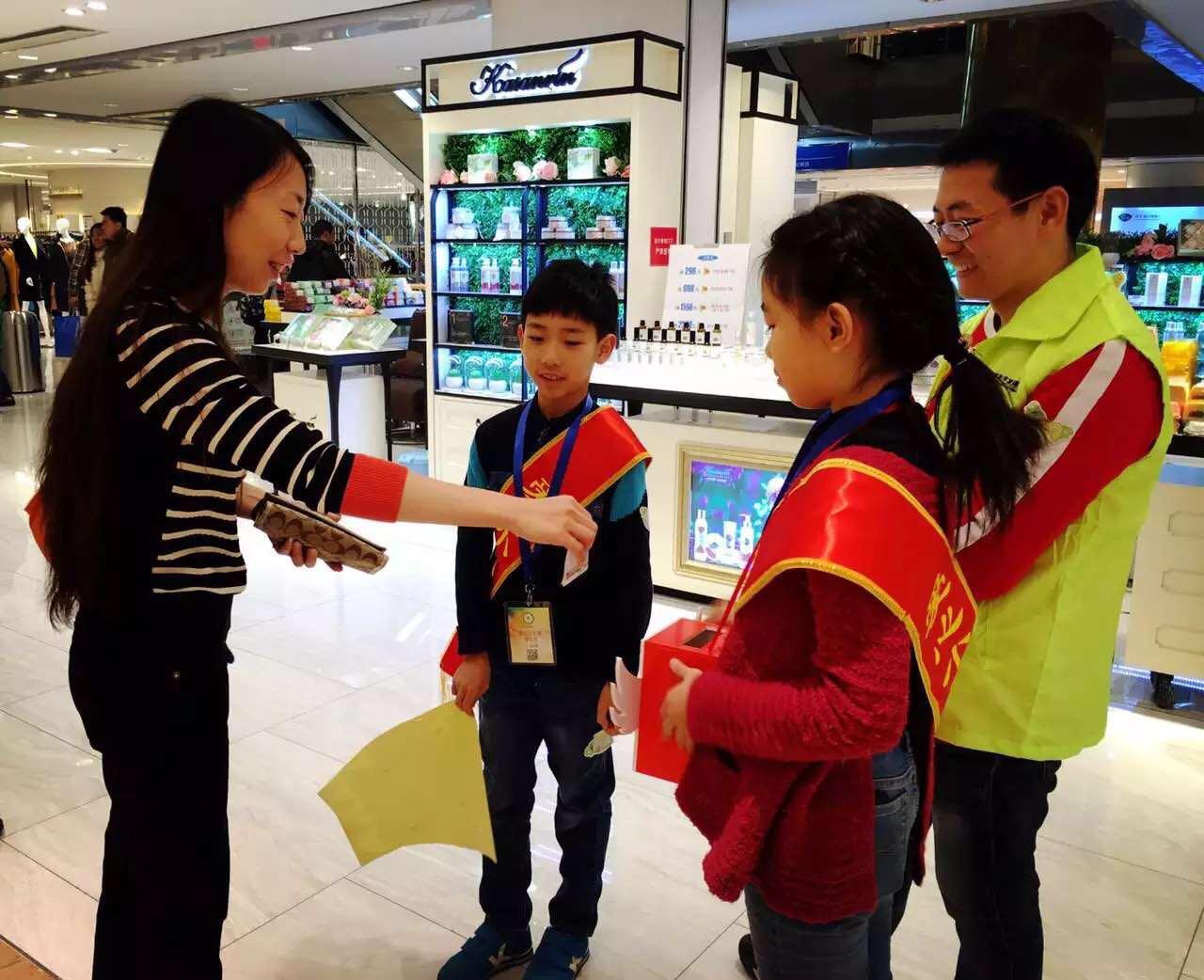 """一群可爱的孩子身披""""爱心小天使""""绶带,手中抱着捐款箱,在向过往的顾客"""