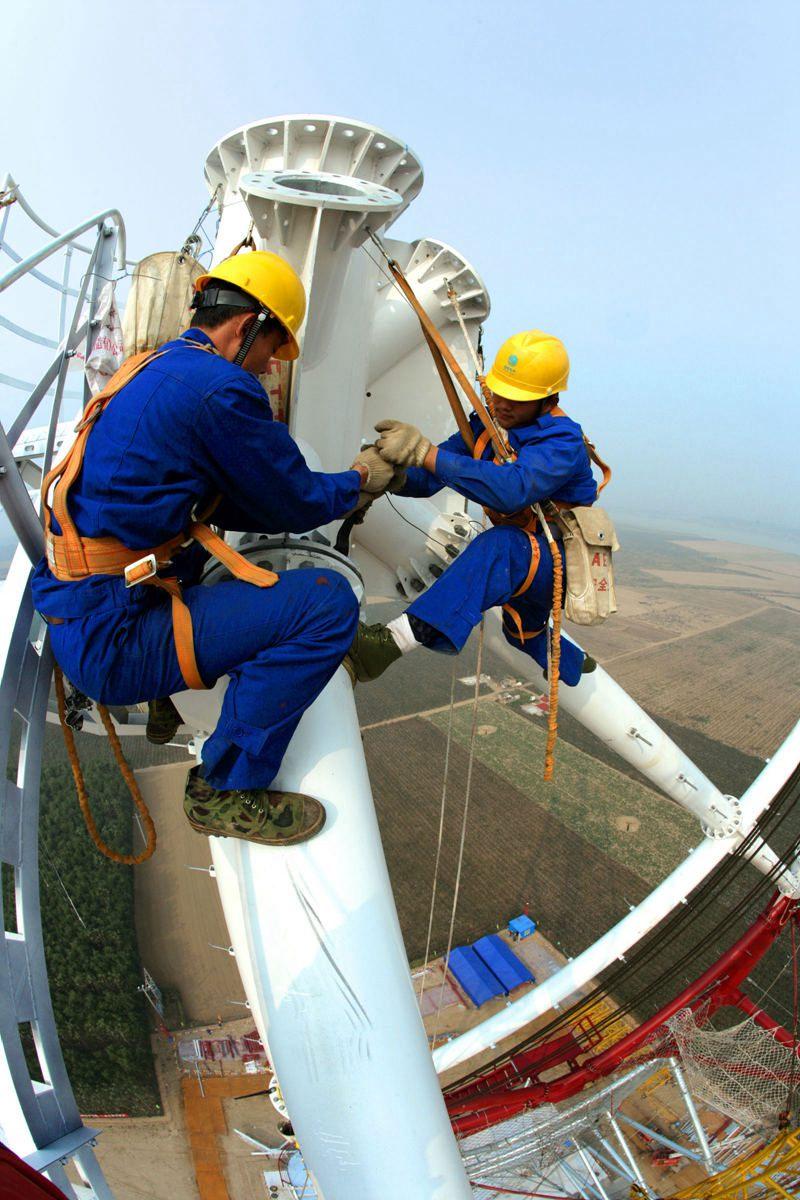 图为特高压工程组塔施工场景,图片由国家电网公司提供
