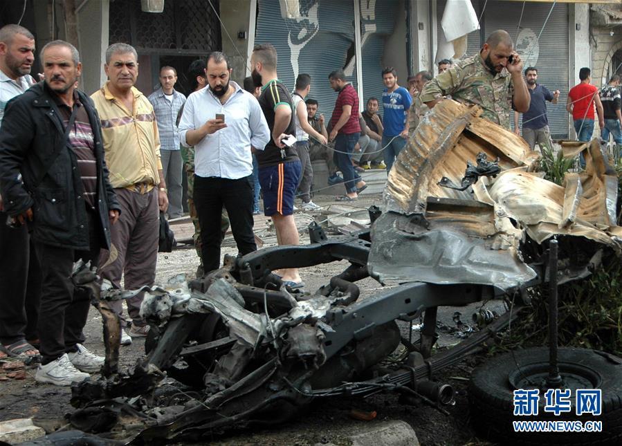 5月23日,在叙利亚霍姆斯,人们聚集在汽车炸弹袭击现场。