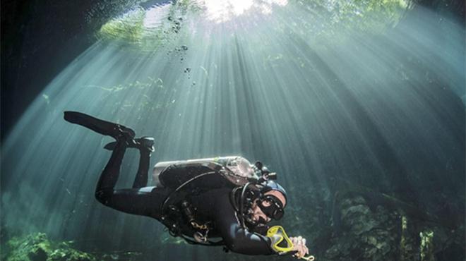 阳光穿越墨西哥水下洞穴 潜水员光束内下潜