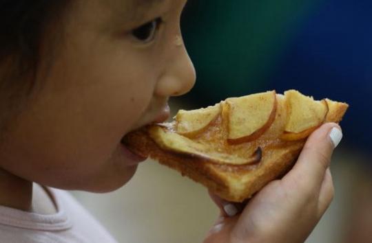 一名小学生吃着用苹果代替鸡蛋制作的烤面包片。