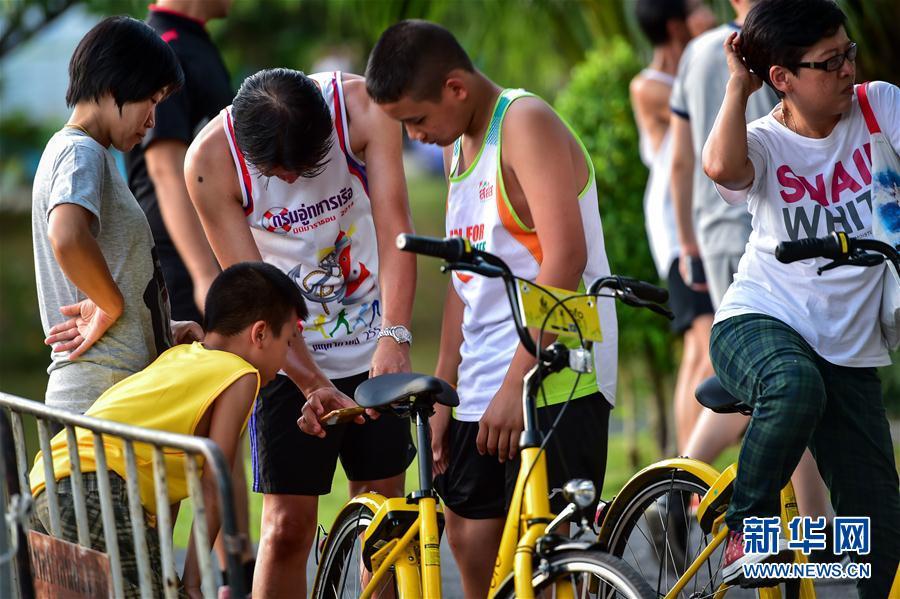 10月5日,在泰国普吉老城区的一处公园,人们用手机解锁ofo小黄车。