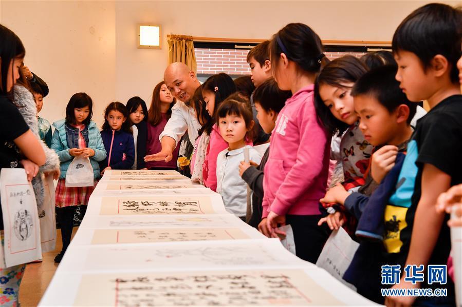 10月19日,在法国圣日耳曼昂莱的让·穆兰小学,学生们观看木版水印作品。