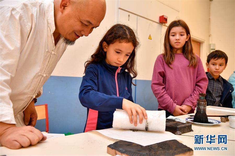 10月19日,在法国圣日耳曼昂莱的让·穆兰小学,学生在魏立中的指导下体验木版水印技艺。