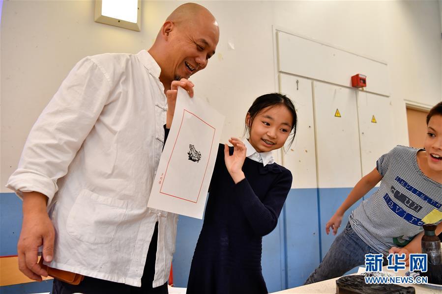 10月19日,在法国圣日耳曼昂莱的让·穆兰小学,一名学生展示亲手拓印的作品。