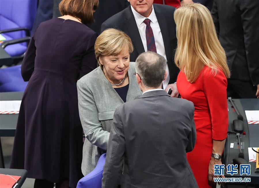 10月24日,在德国首都柏林,德国总理默克尔(中)在会议开始前和与会者交谈。