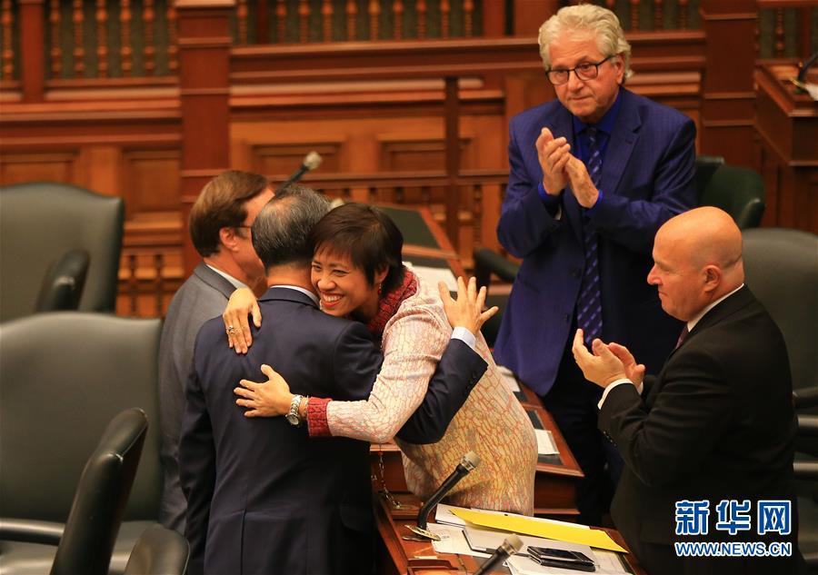10月26日,在加拿大多伦多,安大略省议会议员黄素梅(中)与同事拥抱庆祝动议获通过。