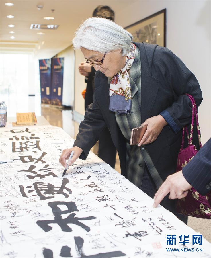 """10月28日,在加拿大多伦多举办的南京大屠杀史料展上,一位参观者在写有""""牢记历史珍爱和平""""字样的书法作品上签名。"""