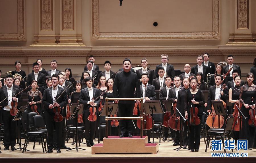 中国国家大剧院音乐艺术总监、国家大剧院管弦乐团音乐总监与首席指挥吕嘉(中)与乐团成员在演出前向观众致意。