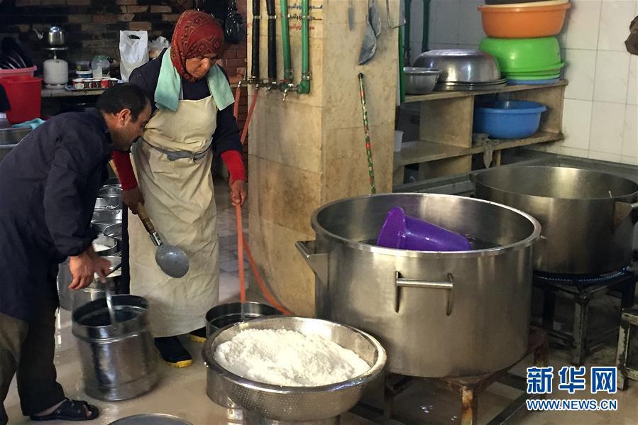 """工人们在由中国政府提供资金援助的""""慈善厨房""""为流离失所者准备食物。"""