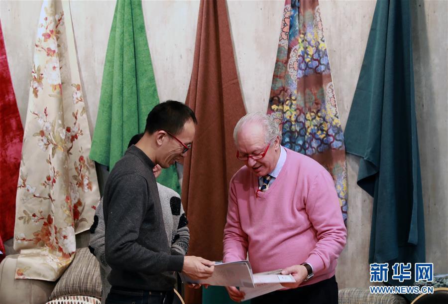 1月11日,在德国法兰克福举行的家用及室内纺织品展览会上,外商在一家中国纺织品厂商展台参观洽谈。