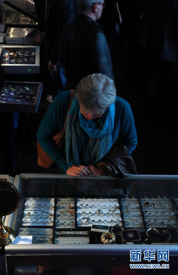 3月11日,在德国法兰克福,人们在第十八届古董钟表珠宝展上选购钟表珠宝。