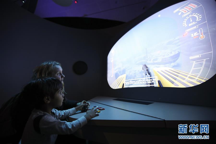 """3月14日,在美国纽约自然历史博物馆举行的""""未见的海洋""""展览上,一对母子操作模拟潜水器探索海底世界。"""