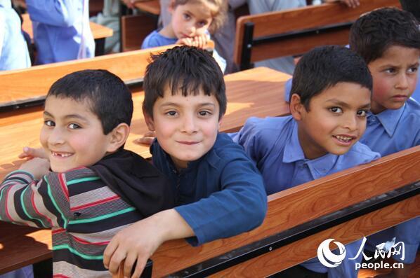 """12日,由中国机械设备工程股份有限公司援建的巴基斯坦北部一所""""友谊中学""""举行新校舍移交仪式,此举将帮助解决几百名儿童的上学问题,推动当地教育事业发展。图为孩子们笑容洋溢,期待搬入新校舍。丁雪真 摄"""