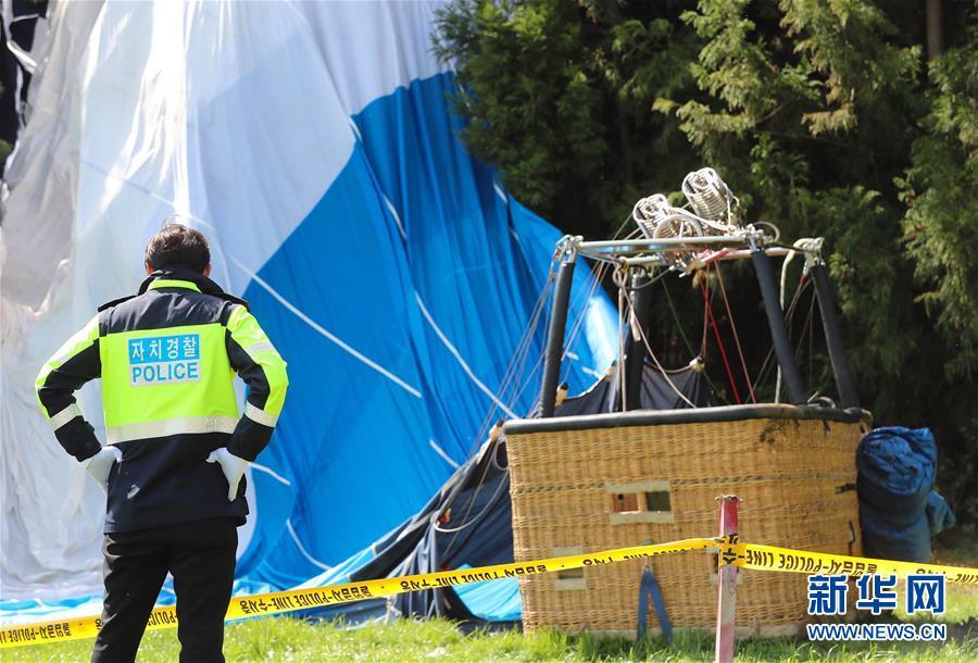 4月12日,在韩国济州西归浦市南元邑新兴里,一名警察在热气球坠落事故现场执勤。