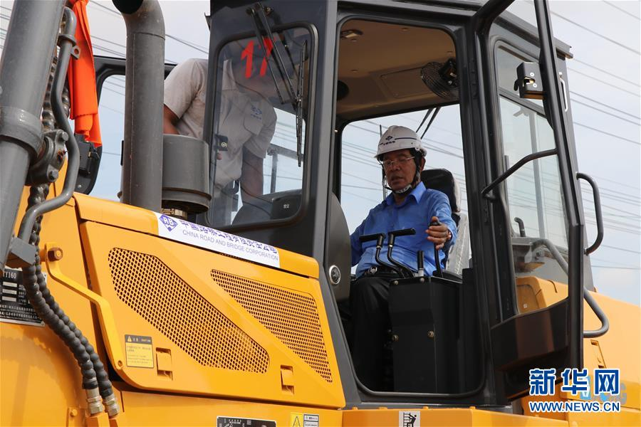 5月7日,在柬埔寨金边,柬埔寨首相洪森(右)在开工仪式上操作推土机。