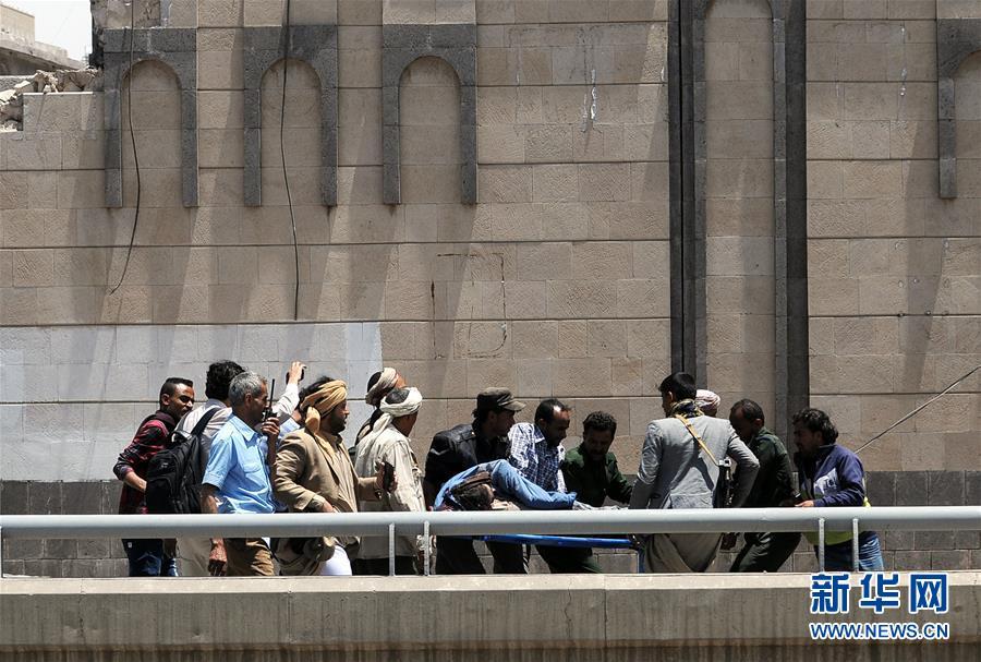 5月7日,在也门萨那,人们抬着一名遭受空袭的伤员。