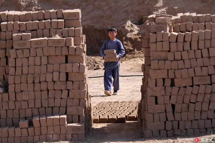 当地时间2018年5月7日,阿富汗赫拉特,几名阿富汗男孩在当地砖窑工作。长年战乱使阿富汗经济迟迟不得好转,教育基础设施十分匮乏,因此,许多家庭将男孩送到当地工厂劳作,以补贴家用。据报告,阿富汗有300至500万儿童无法就学,其中多数为女孩。 (图片来自东方IC 版权所有 请勿转载)