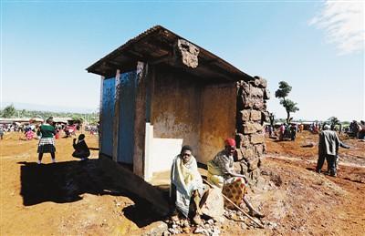 5月10日,在肯尼亚纳库鲁郡,两名幸存者坐在被洪水摧毁的房屋旁。新华社发