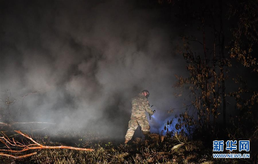 """5月10日,在美国夏威夷帕霍阿镇附近的""""莉拉妮地产""""居民区,一名士兵在第13号裂缝处监测有害气体。"""