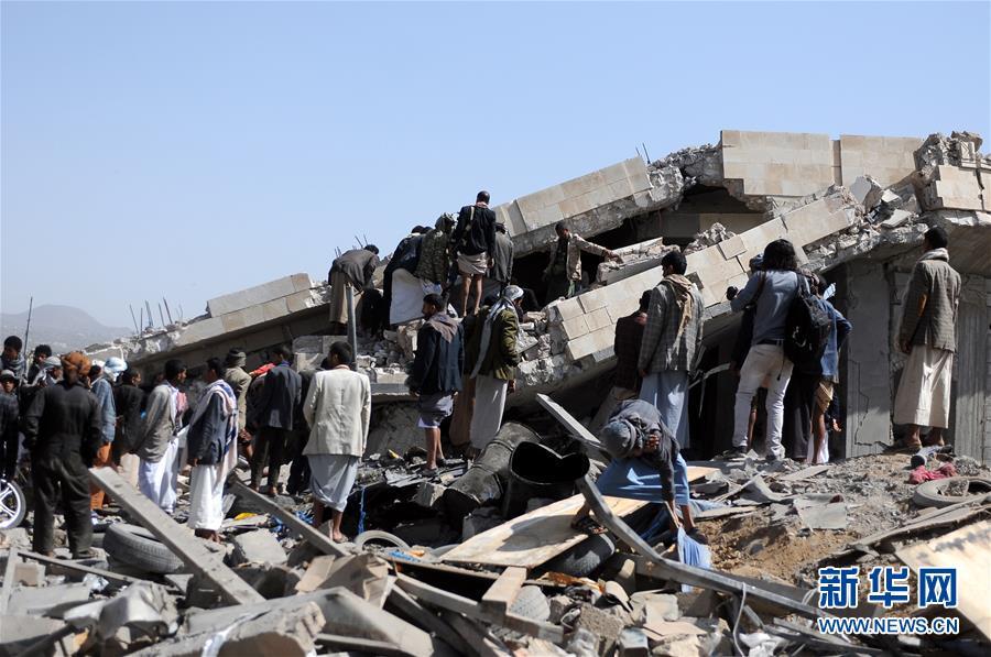 5月10日,在也门首都萨那市郊,人们在废墟中寻找幸存者。