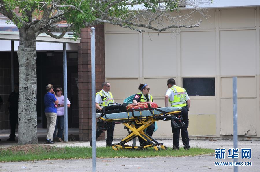 5月18日,在美国得克萨斯州圣菲市,救援人员携带担架在学生临时避难的体育馆外待命。