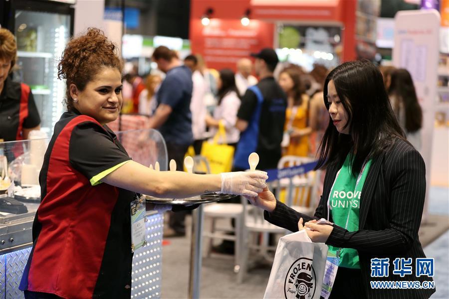 5月21日,在美国芝加哥举行的美国餐饮展上,一名展商给参观者发放试吃样品。