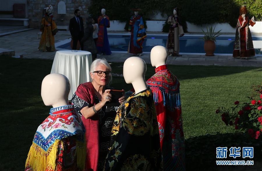 5月22日,在希腊雅典,一位出席捐赠仪式的来宾拍摄捐赠品
