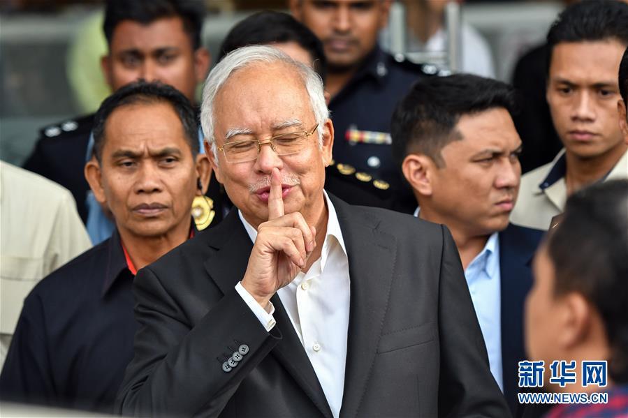 5月24日,在马来西亚普特拉贾亚,马来西亚前总理纳吉布(前)接受问话后离开反腐败委员会