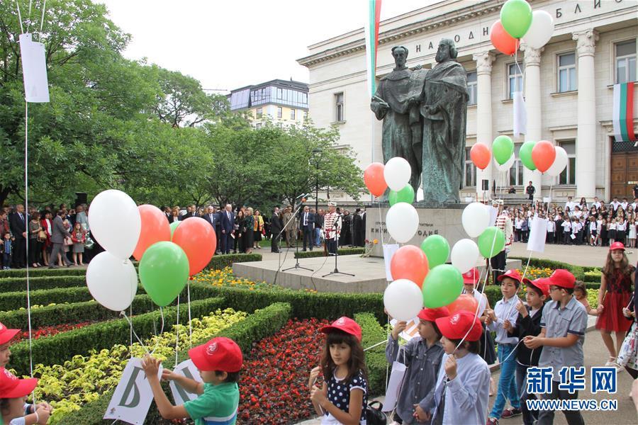 5月24日,在保加利亚首都索菲亚,小学生手举挂着基里尔字母纸牌的彩色气球参加庆祝仪式。