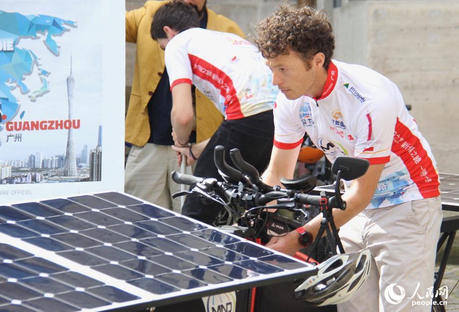 """图为启动仪式上,参与""""一带一路:太阳之旅""""的选手正在调整自己的太阳能车。龚鸣摄"""