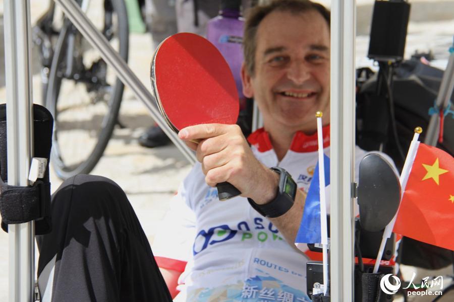 """图为参与""""一带一路:太阳之旅""""的选手保罗在""""座驾""""上向记者展示自己携带的乒乓球拍。龚鸣摄"""