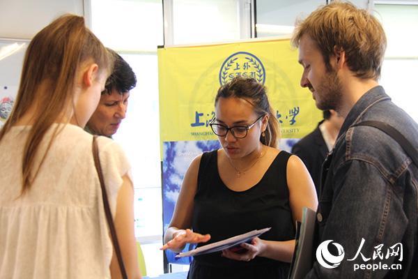 埃娃(右二)说一口流利的汉语,是上海外国语大学展台的志愿者,曾经也在该校交换过一个学期。图为埃娃向法国学生介绍上外的留学生课程项目。龚鸣摄