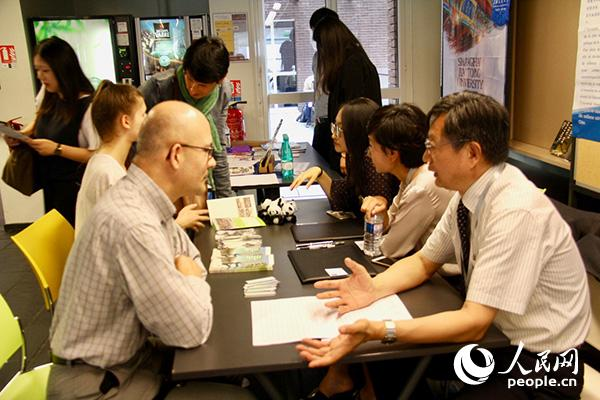 一名法国中文教师正在上北京师范大学展台前咨询情况。龚鸣摄