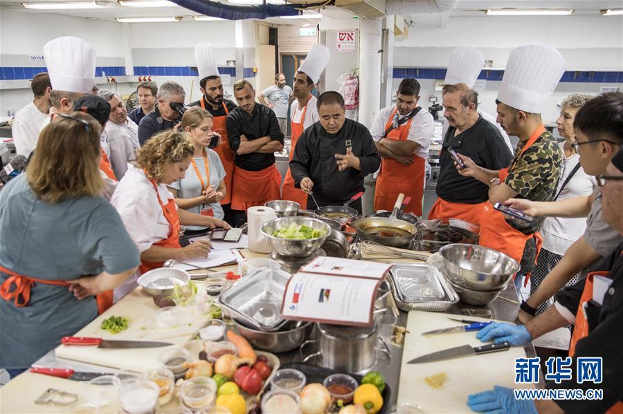 6月18日,在以色列赫兹利亚,中国厨师教以色列厨师做木须肉。