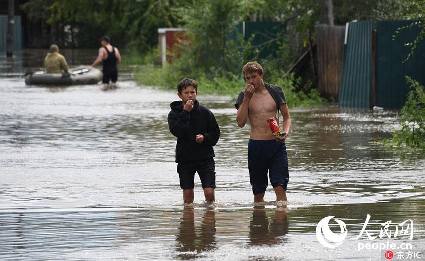 当地时间2018年7月10日,俄罗斯赤塔遭暴雨侵袭导致洪灾,政府宣布进入紧急状态。图为民众在洪水中行走,淡定吃零食。(东方IC版权作品 请勿转载)