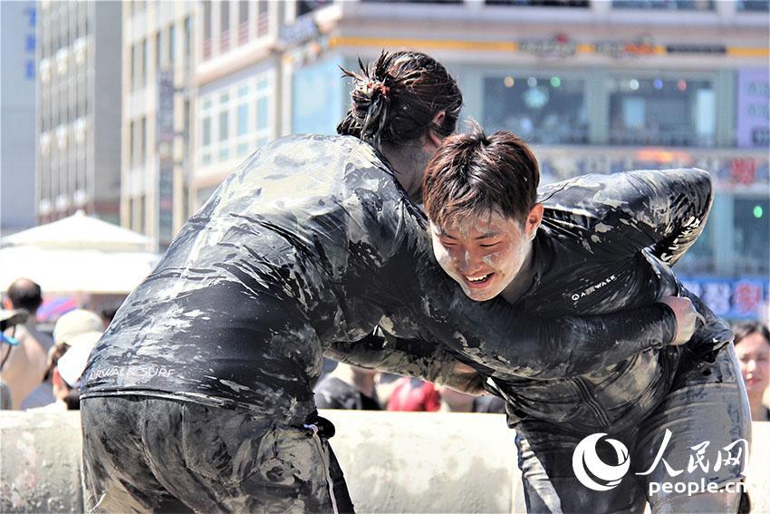 2018年7月13日至22日,第21届韩国保宁泥浆节在忠清南道大川海水浴场举行。游客正在体验泥浆摔跤。 记者 陈尚文摄