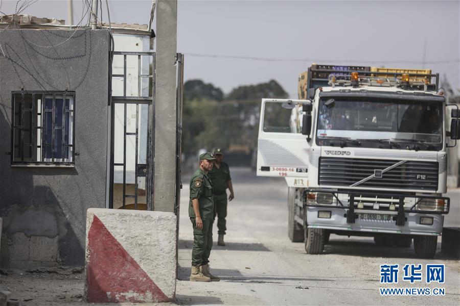 7月17日,在加沙地带东南部与以色列接壤的凯雷姆沙洛姆货运口岸,巴勒斯坦安全人员站在一辆货运卡车旁。