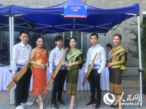 来自老挝的演员在老挝美食展示摊位前合影