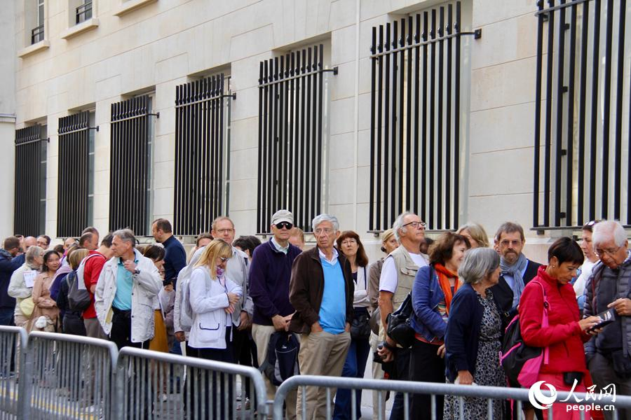 图为民众在中国驻法国使馆外排队等候参观。龚鸣摄