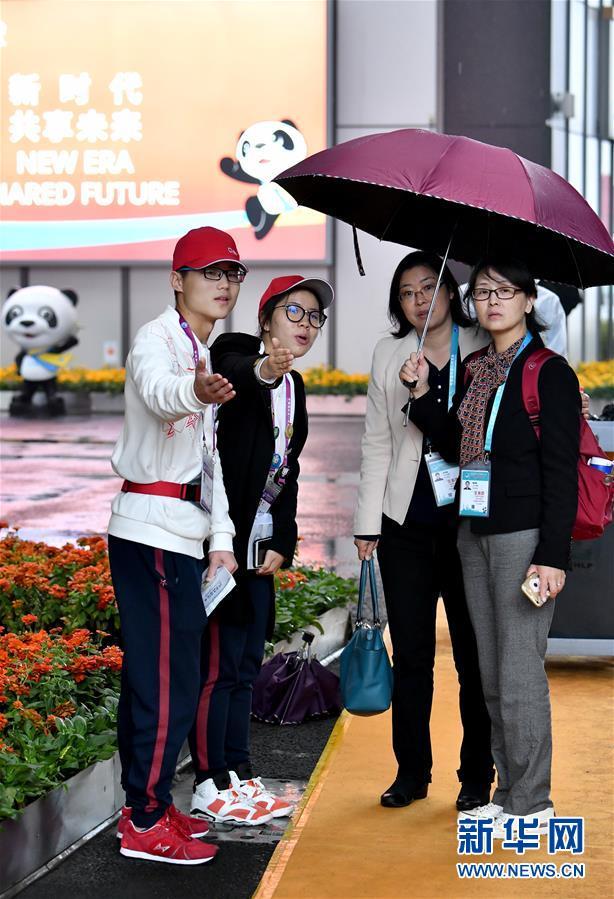 11月7日,进博会志愿者、上海中医药大学学生王杰(左一)和沈昱(左二)在为观众指引道路。 记者 李鑫 摄