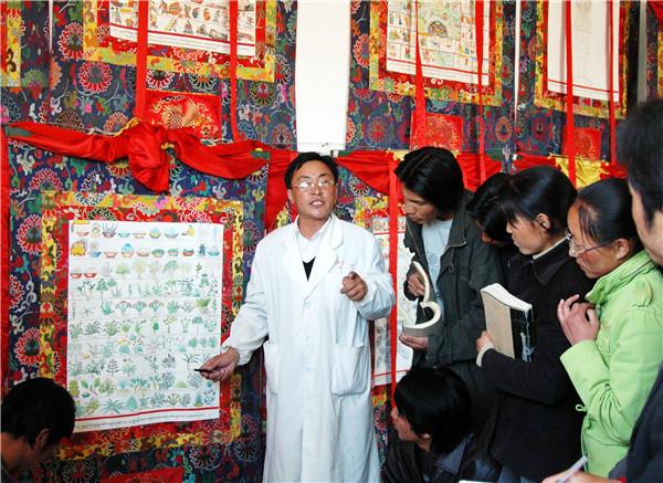 藏医医生向学生介绍在古籍中记载的用于药浴的草药。教科文组织提供