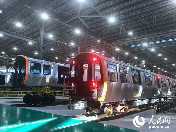图为在美国中车麻省公司春田工厂车辆总装车间,中国中车集团为波士顿地铁生产的始列车下线。李晓宏摄