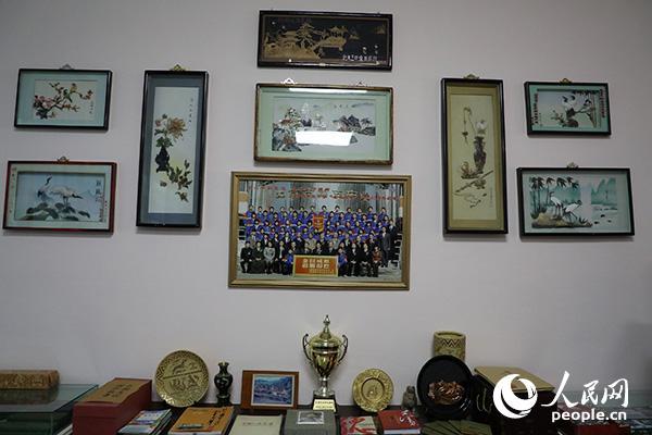 """在东平壤第一中学教学楼一层的陈列室中,挂着一张东平壤第一中学教师代表2010年访问北京五中时与""""金日成班""""师生们的合影。(记者 莽九晨摄)"""