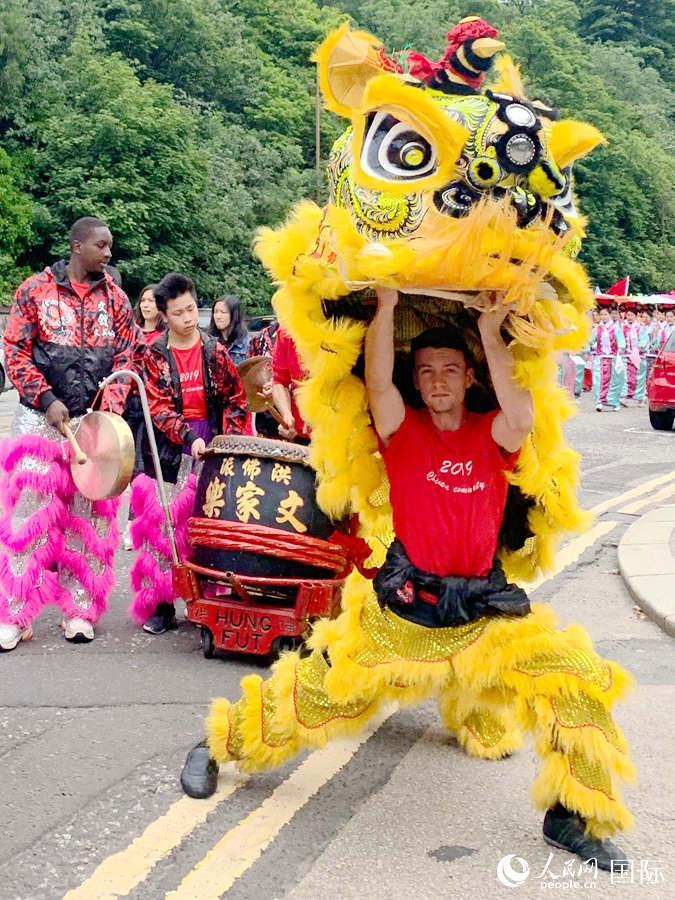 中国方队中一个由苏格兰内地年青人装扮的舞狮。强薇 摄
