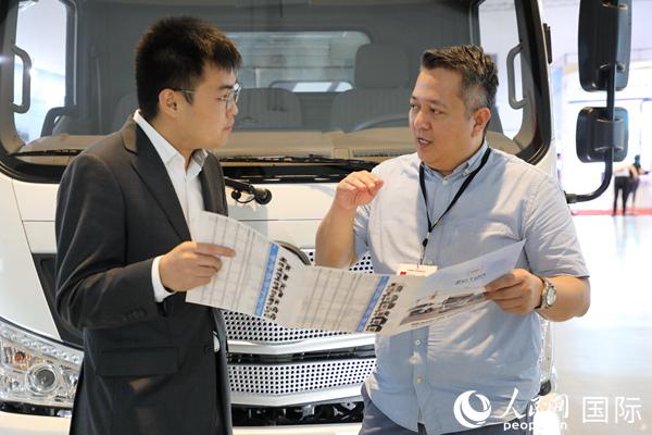 工程展期间,养书阁好,从事菲律宾汽车经销行业的莱维・桑托斯(右)正在和中国汽车品牌福田的工作人员(左)洽谈商务合作。记者赵益普摄