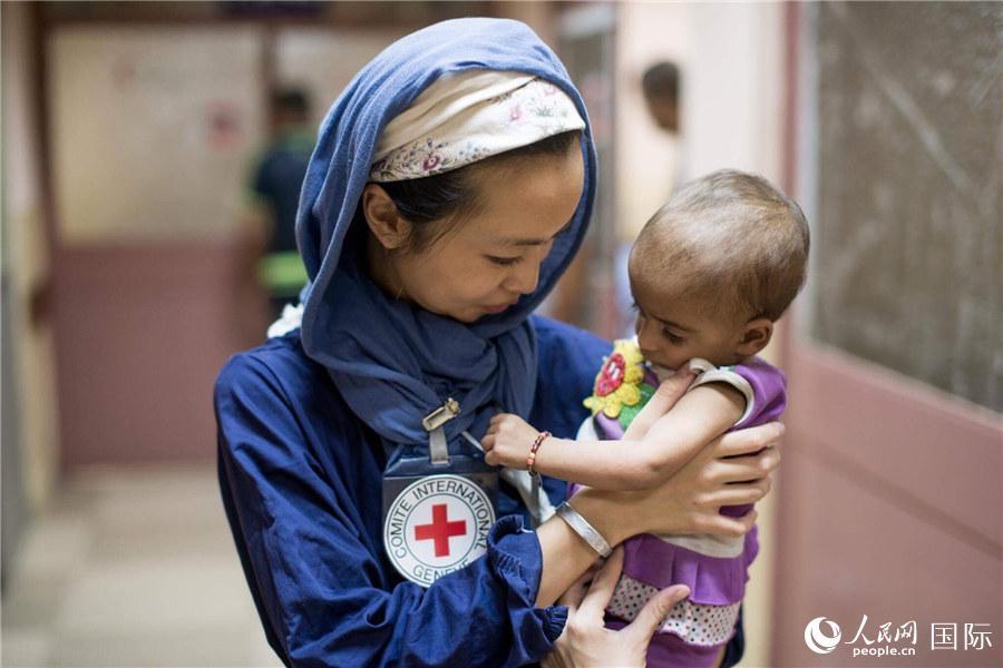 """伊拉克摩苏尔郊外,红十字国际委员会护士曾雅诗抱着一名伊拉克儿童。曾雅诗来自香港,从2016年起为红十字国际委员会工作。看似瘦弱的她,先后在南苏丹、伊拉克、也门等战乱地区参与医疗援助工作。""""女性看似很柔弱,但其实我们是刚柔并济。""""曾雅诗说,在一线的每一天,都感受到大家用心的付出,无论是救援人员还是当地的民众,""""虽然工作或生活环境充满困难,都无碍我们发挥所长。"""""""